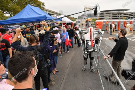 Stock Picture of Comedian and Daily Show contributor, Jordan Klepper (R) speaks with a Donald J. Trump supporter dressed in Terminator cosplay at a campaign rally
