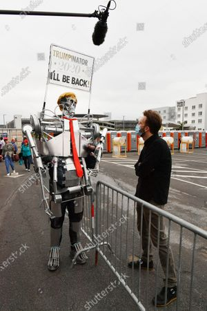Comedian and Daily Show contributor, Jordan Klepper (R) speaks with a Donald J. Trump supporter dressed in Terminator cosplay at a campaign rally