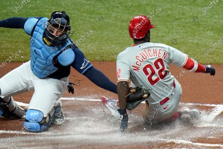 Philadelphia Phillies' Andrew McCutchen (22) scores ahead of the tag by Tampa Bay Rays catcher Mike Zunino on an RBI single by Jean Segura during the first inning of a baseball game, in St. Petersburg, Fla