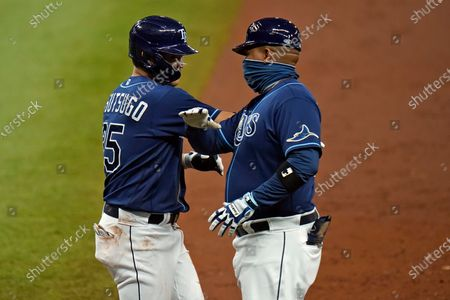 Stock Picture of Tampa Bay Rays' Yoshi Tsutsugo, of Japan, left, celebrates with first base coach Ozzie Timmons after drawing a walk from Philadelphia Phillies' Zack Wheeler during the second inning of a baseball game, in St. Petersburg, Fla