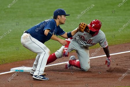 Stock Photo of Philadelphia Phillies' Andrew McCutchen slides into thrid base ahead of the tag by Tampa Bay Rays' Yoshi Tsutsugo, of Japan, during the third inning of a baseball game, in St. Petersburg, Fla. After a review, McCutchen was sent back to second and credited with a double