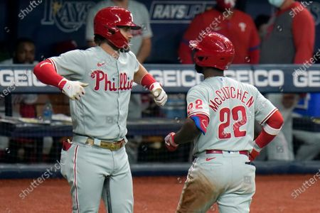 Philadelphia Phillies' Andrew McCutchen (22) celebrates with Bryce Harper after McCutchen hit a solo home run off Tampa Bay Rays relief pitcher Peter Fairbanks during the fifth inning of a baseball game, in St. Petersburg, Fla