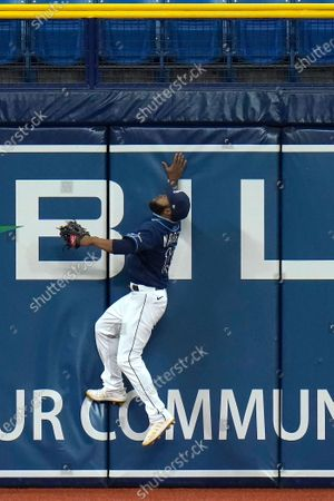 Stock Image of Tampa Bay Rays left fielder Manuel Margot goes up but can't make the catch on a solo home run by Philadelphia Phillies' Andrew McCutchen during the fifth inning of a baseball game, in St. Petersburg, Fla