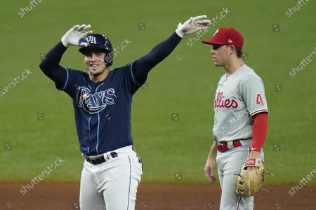Stock Image of Tampa Bay Rays' Willy Adames celebrates after hitting an RBI double off Philadelphia Phillies starting pitcher Zack Wheeler during the fifth inning of a baseball game, in St. Petersburg, Fla. Looking on is Phillies' Scott Kingery (4