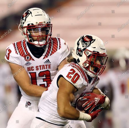 North Carolina State quarterback Devin Leary (13) hands off to running back Jordan Houston (20) for a touchdown run in the second half of an NCAA college football game against Virginia Tech, in Blacksburg, Va