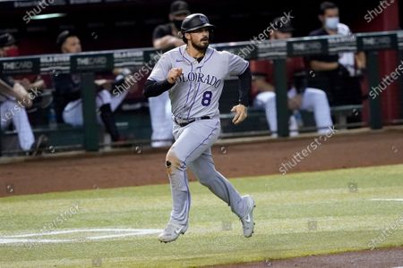 Colorado Rockies' Josh Fuentes (8) scores on a base hit by teammate Daniel Murphy during the fourth inning of a baseball game against the Arizona Diamondbacks, in Phoenix