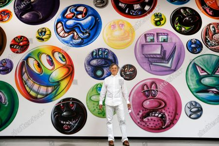 Gallery owner Jeffrey Deitch stands in front of an exhibition titled MOODZ the art of Kenny Scharf on display at the Jeffrey Deitch gallery in the Hollywood section of Los Angeles on . It features two hundred and fifty new circular paintings of faces everyone of them different