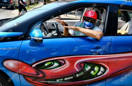 Artist Kenny Scharf wearing a mask poses in his car with one of his paintings during Karbombz!, a rally of about 50 cars all painted by Scharf in the Hollywood section of Los Angeles on . Scharf starting the project in 2013 and has painted 260 cars around the world, about 100 of which are in Los Angeles. Scharf currently has an exhibition on view at Jeffrey Deitch gallery with two hundred fifty new paintings of faces, all of them different