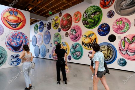 Gallery goers overlook an exhibition titled MOODZ, the art of Kenny Scharf on display at the Jeffrey Deitch gallery in the Hollywood section of Los Angeles on . It features two hundred and fifty new circular paintings of faces everyone of them different by Scharf