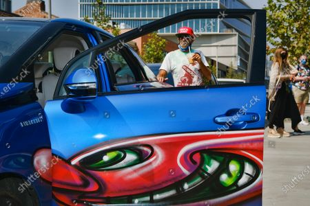 Artist Kenny Scharf poses on his car with one of his paintings during Karbombz!, a rally of cars all painted by Scharf in the Hollywood section of Los Angeles on . Scharf starting the project in 2013 and has painted 260 cars around the world, about 100 of which are in Los Angeles. Scharf currently has an exhibition on view at Jeffrey Deitch gallery with two hundred fifty new paintings of faces, all of them different