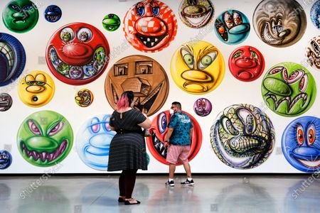 """Visitors view an exhibition entitled, """"MOODZ,"""" the art of Kenny Scharf, on display at the Jeffrey Deitch gallery in the Hollywood section of Los Angeles, . It features 250 new circular paintings of faces, each one of them different, created by Scharf"""