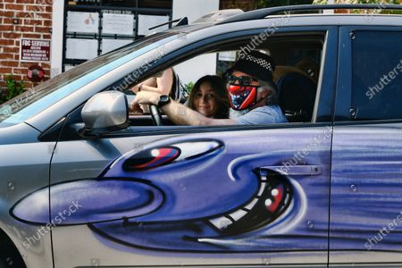 """Masked driver in a van bombed by artist Kenny Scharf for his """"Karbombz!"""" project drives down the street during a rally in the Hollywood section of Los Angeles, . Scharf started the project in 2013 and has painted 260 cars around the world, about 100 of which are in Los Angeles. He currently has an exhibition on view at Jeffrey Deitch gallery featuring 250 new paintings of faces, each of them different"""