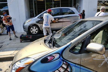 Stock Image of Artist Kenny Scharf paints cars in front of the Jeffrey Deitch gallery after a rally of about about 50 cars, all painted by Scharf, gathered in the Hollywood section of Los Angeles, . Scharf started the project in 2013 and has painted 260 cars around the world, about 100 of which are in Los Angeles. He currently has an exhibition on view at Jeffrey Deitch gallery, featuring 250 new paintings of faces, each one different