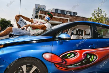 """Stock Photo of Artist Kenny Scharf poses on his car with one of his paintings during the """"Karbombz!"""" rally of about 50 cars, all painted by Scharf, in the Hollywood section of Los Angeles, . Scharf started the project in 2013 and has painted 260 cars around the world, about 100 of which are in Los Angeles. He currently has an exhibition on view at Jeffrey Deitch gallery, featuring 250 new paintings of faces, each one different"""