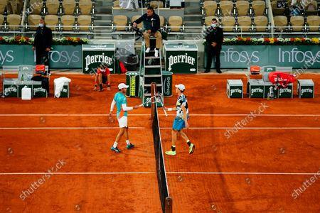 David Goffin congratulates Jannik Sinner at the net after their Men's Singles first round match on Philippe Chatrier Court