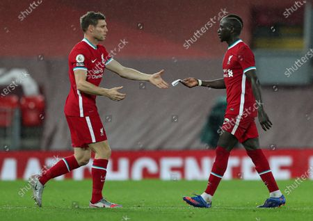 Sadio Mane of Liverpool hands the captains arm band to James Milner