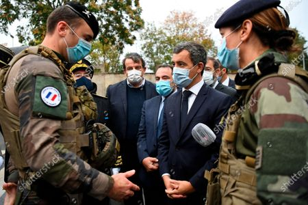 Stock Image of French Interior Minister Gerald Darmanin, center left, Joel Mergui, center left behind, President of the Israelite Central Consistory of France talk with soldiers before a visit to the synagogue of Boulogne-Billancourt, outside Paris, . France's interior minister promised to protect France's Jewish community from extremists after a double stabbing in Paris blamed on Islamic terrorism. France has Europe's largest Jewish community