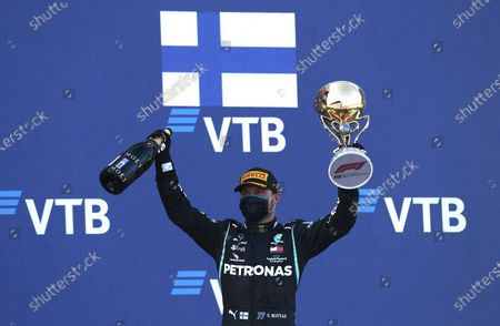 Mercedes driver Valtteri Bottas of Finland holds up the trophy on the podium after winning the Russian Formula One Grand Prix, at the Sochi Autodrom circuit, in Sochi, Russia
