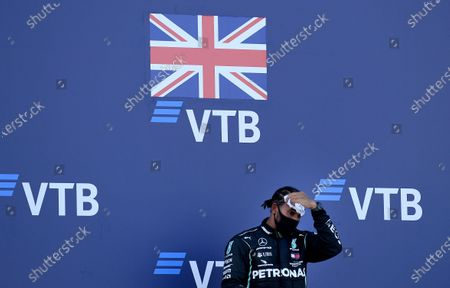 Mercedes driver Lewis Hamilton of Britain wipes his forehead as he stands on the podium after placing third in the Russian Formula One Grand Prix, at the Sochi Autodrom circuit, in Sochi, Russia