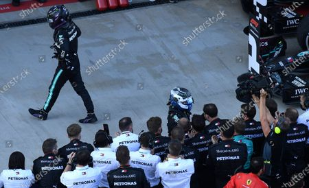 Mercedes driver Lewis Hamilton of Britain, left, walks away as Mercedes driver Valtteri Bottas of Finland is congratulated by the crew after placing first in the Russian Formula One Grand Prix, at the Sochi Autodrom circuit, in Sochi, Russia, . Hamilton places third in the event