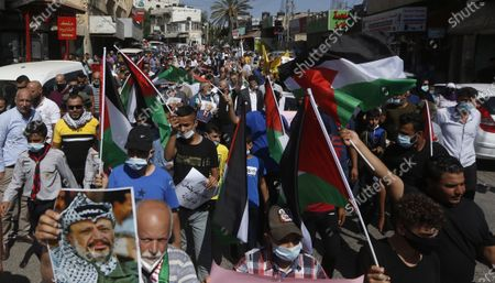 Stock Picture of Palestinians wave their national flags and hold pictures of the late Yasser Arafat during a protest against the peace agreement to establish diplomatic ties between Israel, Bahrain and the United Arab Emirates, in the West Bank city Tubas, 27 September 2020.