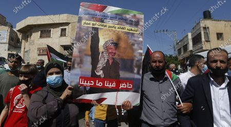 Palestinians hold a photo of late Palestinian leader Yasser Arafat during a protest against the peace agreement to establish diplomatic ties between Israel, Bahrain and the United Arab Emirates, in the West Bank city Tubas 27  September 2020.