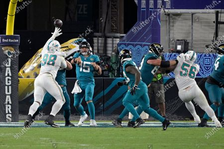 Jacksonville Jaguars quarterback Gardner Minshew (15) throws to running back James Robinson over Miami Dolphins defensive tackle Raekwon Davis (98) during the second half of an NFL football game, in Jacksonville, Fla