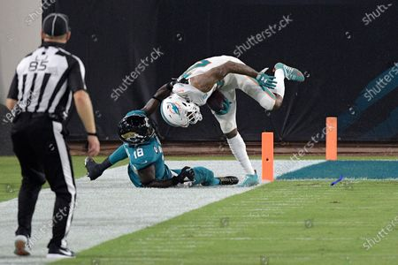 Miami Dolphins cornerback Xavien Howard (25) is tackled by Jacksonville Jaguars wide receiver Chris Conley (18) after intercepting a pass during the second half of an NFL football game, in Jacksonville, Fla