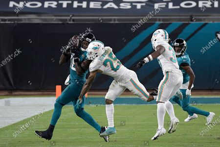 Jacksonville Jaguars wide receiver Chris Conley catches a pass in front of Miami Dolphins cornerback Xavien Howard (25) during the second half of an NFL football game, in Jacksonville, Fla