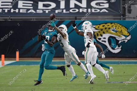 Jacksonville Jaguars wide receiver Chris Conley, left, catches a pass in front of Miami Dolphins cornerback Xavien Howard (25) during the second half of an NFL football game, in Jacksonville, Fla