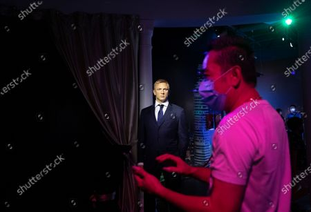 Stock Picture of A visitor looks at a wax figurine of English actor Daniel Craig at Madame Tussauds Singapore in Sentosa, Singapore, 27 September 2020. As the Covid-19 pandemic batters the tourism industry in Singapore with borders remaining largely closed top overseas visitors, the city state is turning to domestic tourists instead. The Singapore Tourism Board has launched a campaign in July to entice Singapore residents to spend on local hotels and attractions and rediscover the island. World Tourism Day is celebrated on 27 September annually.