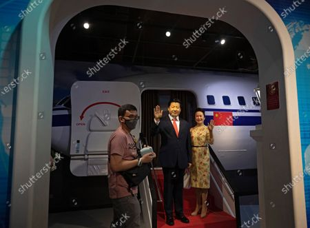 Stock Photo of A visitor walk past wax figurines of Chinese President Xi Jinping and his wife Peng Liyuan at Madame Tussauds Singapore in Sentosa, Singapore, 27 September 2020. As the Covid-19 pandemic batters the tourism industry in Singapore with borders remaining largely closed top overseas visitors, the city state is turning to domestic tourists instead. The Singapore Tourism Board has launched a campaign in July to entice Singapore residents to spend on local hotels and attractions and ÔrediscoverÕ the island. World Tourism Day is celebrated on 27 September annually.