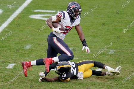 Houston Texans running back David Johnson (31) gets over Pittsburgh Steelers cornerback Mike Hilton (28) on a run in the second half of an NFL football game, in Pittsburgh