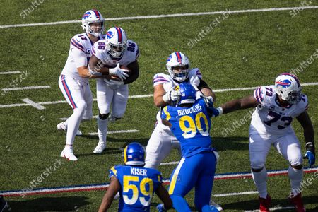Buffalo Bills quarterback Josh Allen (17) hands the ball to running back Devin Singletary (26) during the third quarter of an NFL football game against the Los Angeles Rams, in Orchard Park, N.Y