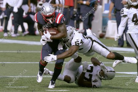New England Patriots running back Sony Michel, left, tries to escape the grasp of Las Vegas Raiders linebacker Raekwon McMillan (54) and defensive back Trayvon Mullen (27) in the second half of an NFL football game, in Foxborough, Mass