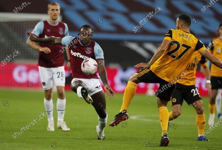 Michail Antonio (L) of West Ham United in action against Romain Saiss of Wolverhampton during the English Premier League match between West Ham United and Wolverhampton Wanderers in London, Britain, 27 September 2020.