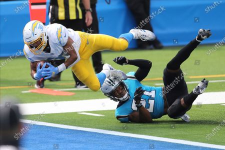 Los Angeles Chargers running back Austin Ekeler (30) leaps into the end zone over Carolina Panthers outside linebacker Jeremy Chinn (21) for a touchdown during an NFL football game, in Inglewood, Calif