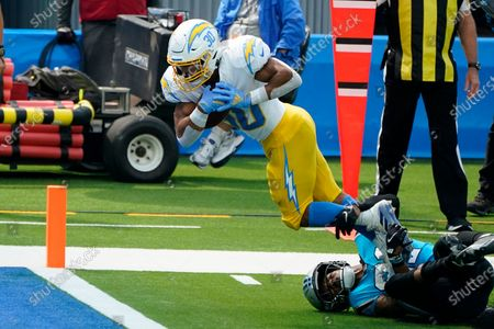 Los Angeles Chargers running back Austin Ekeler (30) scores a touchdown over Carolina Panthers outside linebacker Jeremy Chinn (21) during the first half of an NFL football game, in Inglewood, Calif