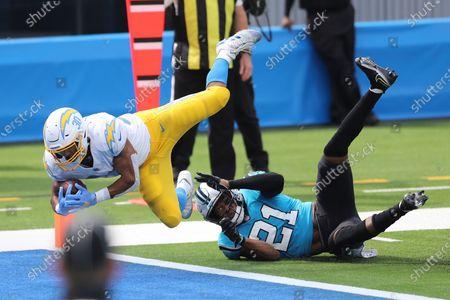 Stock Photo of Los Angeles Chargers running back Austin Ekeler (30) leaps into the end zone over Carolina Panthers outside linebacker Jeremy Chinn (21) for a touchdown during an NFL football game, in Inglewood, Calif
