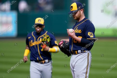 Milwaukee Brewers starting pitcher Brett Anderson looks down at his hand before leaving with an injury during the third inning of a baseball game against the St. Louis Cardinals, in St. Louis