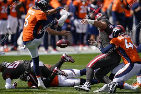Tampa Bay Buccaneers defensive end Pat O'Connor, right, blocks a punt by Denver Broncos punter Sam Martin, left, during the second half of an NFL football game, in Denver