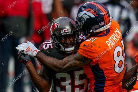 Tampa Bay Buccaneers cornerback Jamel Dean (35) is blocked by Denver Broncos wide receiver Tim Patrick (81) during an NFL football game, in Denver