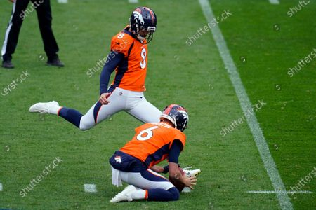 Denver Broncos kicker Brandon McManus kicks a field goal as Sam Martin holds during the first half of an NFL football game against the Tampa Bay Buccaneers, in Denver
