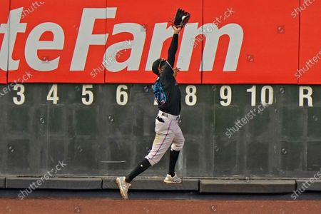 Miami Marlins left fielder Magneuris Sierra (34) makes a leaping catch against the left field scoreboard to rob New York Yankees' Gleyber Torres of a multi-base hit during the ninth inning of a baseball game, at Yankee Stadium in New York