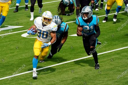 Los Angeles Chargers running back Austin Ekeler (30) runs for a touchdown past Carolina Panthers free safety Tre Boston (33) and outside linebacker Jeremy Chinn (21) during the first half of an NFL football game, in Inglewood, Calif