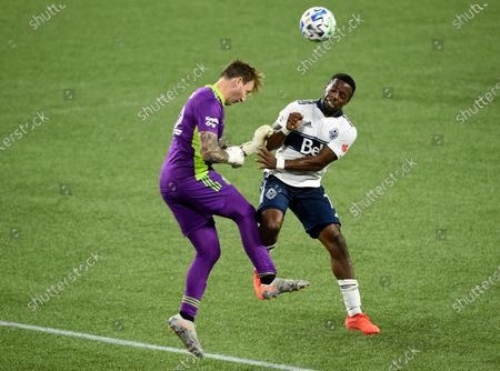 Portland Timbers goalkeeper Steve Clark, left, heads the ball away from Vancouver Whitecaps forward Cristian Dajome during the second half of an MLS soccer match in Portland, Ore., . The Timbers won 1-0