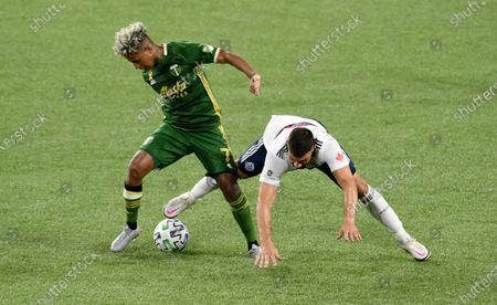 Stock Photo of Portland Timbers forward Andy Polo, left, and Vancouver Whitecaps forward Lucas Cavallini go after the ball during the second half of an MLS soccer match in Portland, Ore., . The Timbers won 1-0