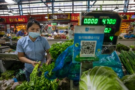 A woman sales vegetables as a wet market, with a Alipay QR payment code displayed at her booth, close to the Ant Group headquarters in Hangzhou, China, 27 September 2020 (issued 28 September 2020). Ant Group is the parent company of China's largest mobile payments business Alipay and leading provider of financial services technology. The Alipay mobile application serves over 1 billion annual active users, according to the company. Ant group is an affiliate company of the Alibaba Group founded by billionaire Jack Ma and it is preparing a simultaneous initial public offering (IPO) in Hong Kong and Shanghai.