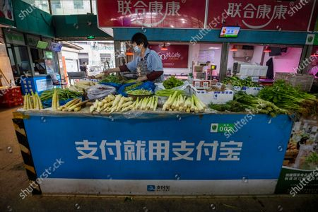 A woman sales vegetables as a wet market, with a Alipay QR payment code and advertisement banner displayed at her booth, close to the Ant Group headquarters in Hangzhou, China, 27 September 2020 (issued 28 September 2020). Ant Group is the parent company of China's largest mobile payments business Alipay and leading provider of financial services technology. The Alipay mobile application serves over 1 billion annual active users, according to the company. Ant group is an affiliate company of the Alibaba Group founded by billionaire Jack Ma and it is preparing a simultaneous initial public offering (IPO) in Hong Kong and Shanghai.