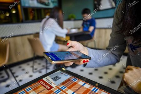 A woman uses her mobile phone to scan a code with Alipay application to view the menu and for payment, in restaurant in the Ant Group headquarters in Hangzhou, China, 27 September 2020 (issued 28 September 2020). Ant Group is the parent company of China's largest mobile payments business Alipay and leading provider of financial services technology. The Alipay mobile application serves over 1 billion annual active users, according to the company. Ant group is an affiliate company of the Alibaba Group founded by billionaire Jack Ma and it is preparing a simultaneous initial public offering (IPO) in Hong Kong and Shanghai.